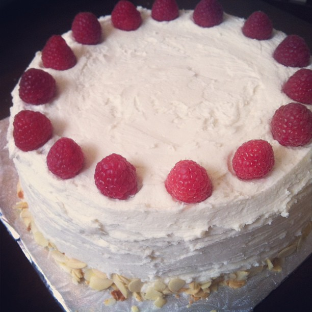 vanilla cake filled with raspberry jam, topped with fresh raspberries, and some toasted almonds. vegan, gluten and soy free.